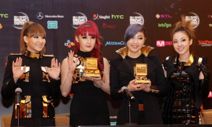 2NE1 members showing their awards during the 2011 Mnet Asian Music Awards.