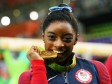 Gold medalist Simone Biles of the United States poses for photographs.